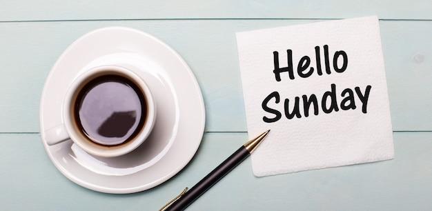 하늘색 나무 쟁반에는 흰색 컵의 커피, 손잡이, hello sunday라고 적힌 냅킨이 있습니다.