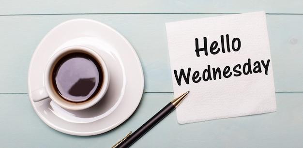 水色の木製トレイには、白い一杯のコーヒー、取っ手、そしてhellowednesdayと書かれたナプキンがあります。