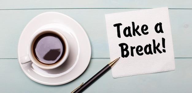 На голубом деревянном подносе есть белая чашка кофе, ручка и салфетка с надписью «сделайте перерыв».