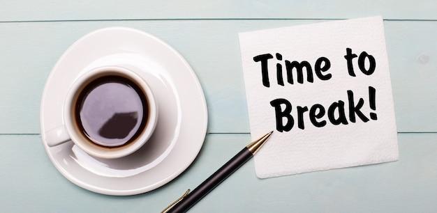 На светло-голубом деревянном подносе есть белая чашка кофе, ручка и салфетка с надписью «время перерыв».
