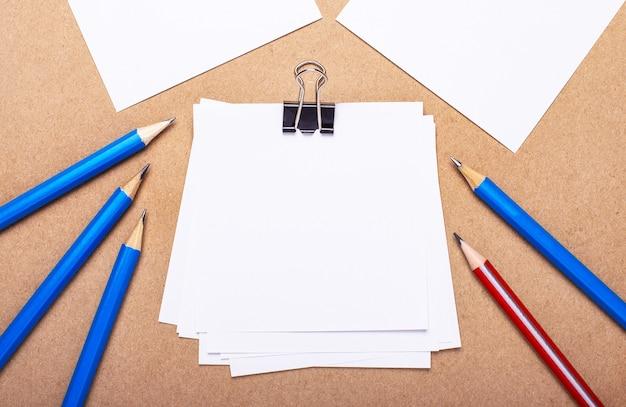 薄茶色の背景に、青と赤の鉛筆とテキストを挿入するスペースのある白い紙。レンプレート。