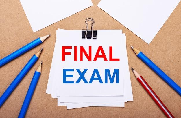 薄茶色の背景に、青と赤の鉛筆と白い紙にfinalexamというテキストがあります