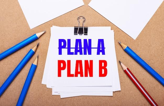 На светло-коричневом фоне синие и красные карандаши и белая бумага с текстом план б.