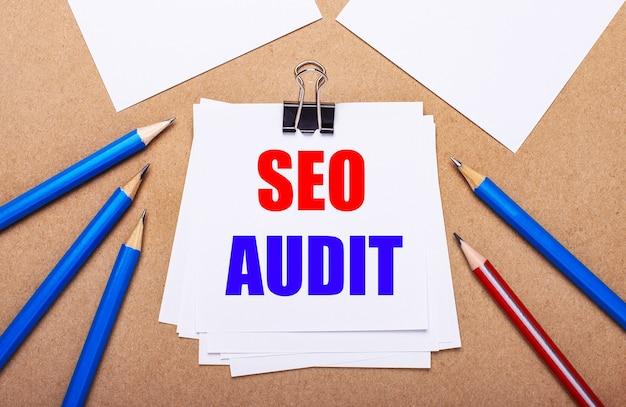 На светло-коричневом фоне синие и красные карандаши и белая бумага с текстом seo audit.