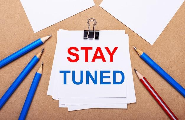 薄茶色の背景に、青と赤の鉛筆と白い紙に「staytuned」というテキストが表示されます