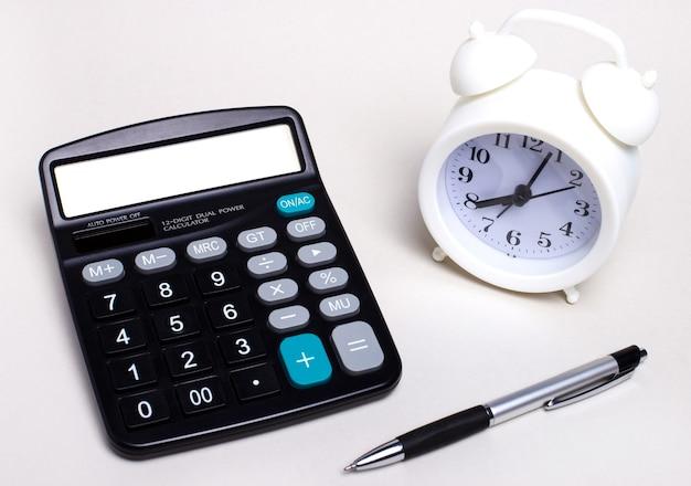 明るいデスクトップには、黒い電卓、ペン、白い目覚まし時計があります。ビジネスコンセプト