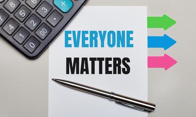 밝은 회색 배경에 계산기, everyone matters라는 텍스트가 있는 흰색 시트, 펜 및 밝은 색 스티커. 위에서 보기