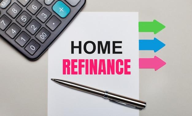 На светло-сером фоне калькулятор, белый лист с текстом home refinance, ручка и яркие разноцветные наклейки. вид сверху