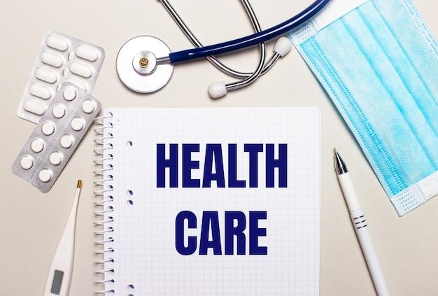 明るい灰色の背景に、水色の使い捨てフェイスマスク、聴診器、電子体温計、丸薬、ペン、ヘルスケアの碑文が書かれたノート。医療コンセプト