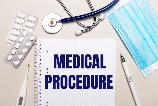 明るい灰色の背景に、水色の使い捨てフェイスマスク、聴診器、電子体温計、丸薬、ペン、および「医療手順」と書かれたノート。医療コンセプト