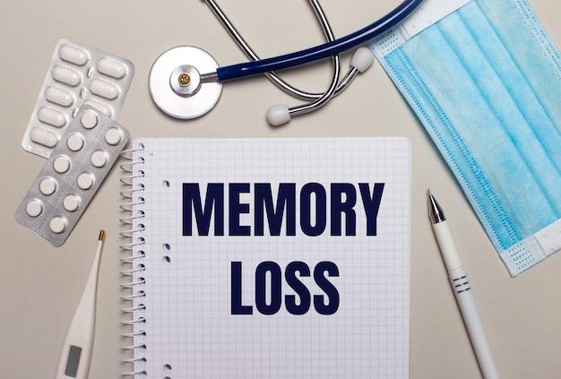 明るい灰色の背景に、水色の使い捨てフェイスマスク、聴診器、電子体温計、丸薬、ペン、memorylossと書かれたノート。医療の概念