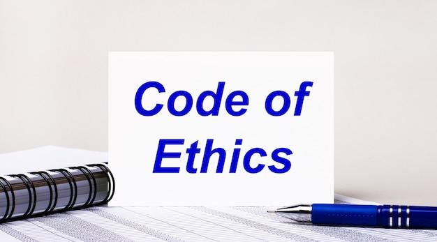 明るい灰色の背景に、ノートブック、青いペン、および倫理規定のテキストが記載された1枚の紙。ビジネスコンセプト