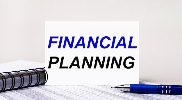 На светло-сером фоне блокнот, синяя ручка и лист бумаги с текстом финансовое планирование. бизнес-концепция