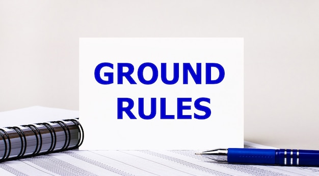 На светло-сером фоне блокнот, синяя ручка и лист бумаги с текстом «правила назначения». бизнес-концепция