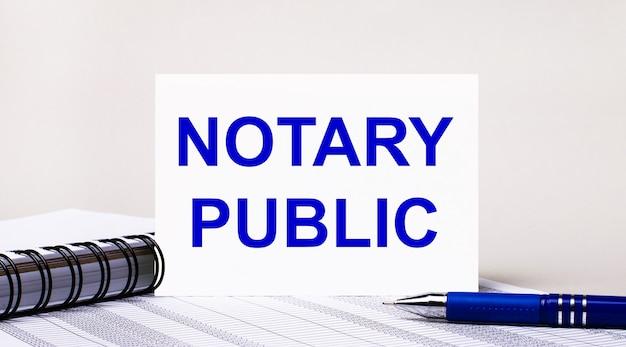 На светло-сером фоне блокнот, синяя ручка и лист бумаги с текстом «нотариус». бизнес-концепция