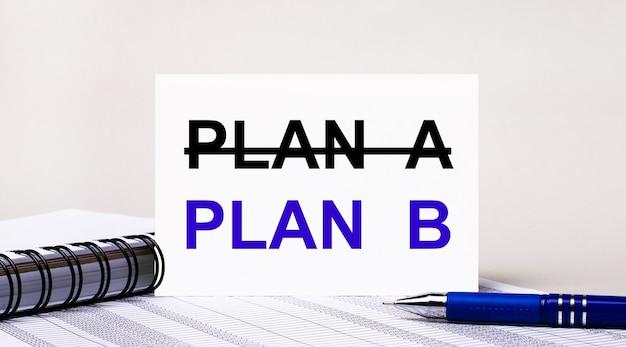 明るい灰色の背景に、ノートブック、青いペン、およびテキストplanbが付いた1枚の紙。ビジネスコンセプト