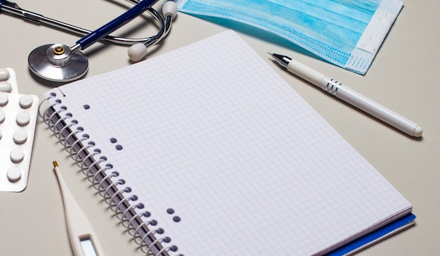 На светло-сером фоне стетоскоп, одноразовая маска для лица, электронный градусник, таблетки и ручка с блокнотом. медицинская концепция