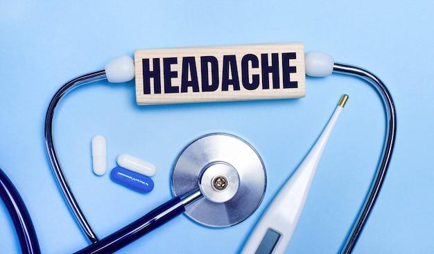 На светло-сером фоне стетоскоп, электронный градусник, таблетки, деревянный брусок с надписью «головная боль». медицинская концепция.
