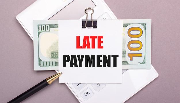 明るい灰色の背景に、白い電卓、現金ドル、およびlatepaymentというテキストが記載された1枚の紙。ビジネスコンセプト