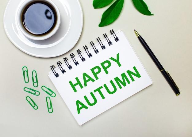 明るい灰色の背景に、白い一杯のコーヒー、緑色のペーパークリップ、植物の緑色の葉、そしてhappyautumnという言葉が書かれたペンとノート。