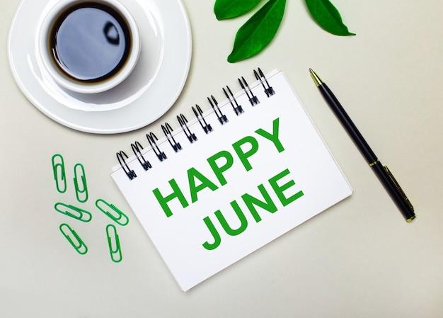 На светло-сером фоне белая чашка кофе, зеленые скрепки и зеленый лист растения, а также ручка и блокнот с надписью happy june.