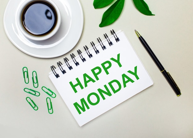 밝은 회색 배경에 흰색 컵의 커피, 녹색 종이 클립 및 식물의 녹색 잎, 펜과 노트북에 happy monday라는 단어가 있습니다.
