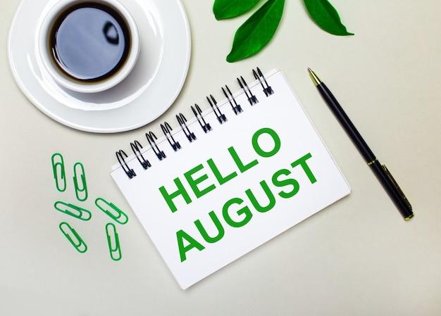 明るい灰色の背景に、白い一杯のコーヒー、緑色のペーパークリップ、植物の緑色の葉、そしてhelloaugustという言葉が書かれたペンとノート。