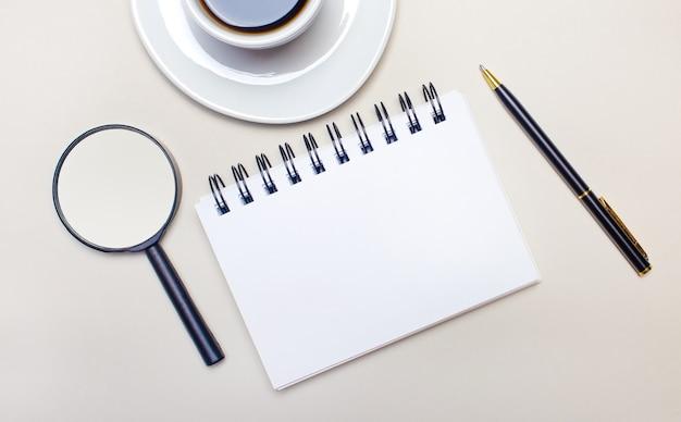 明るい灰色の背景に、コーヒーの入った白いカップ、虫眼鏡、ペン、テキストやイラストを挿入する場所のある空白のノートブック。