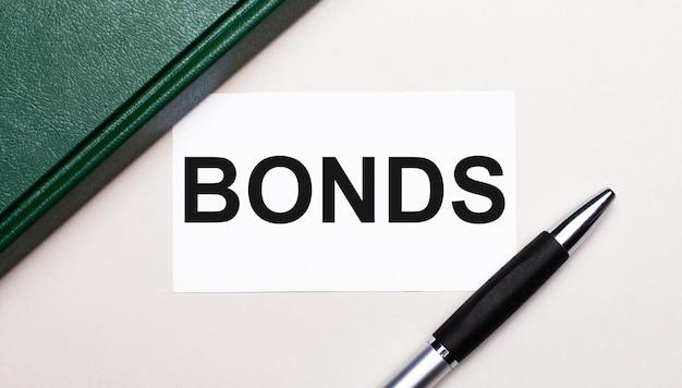 На светло-сером фоне лежит ручка, зеленый блокнот и белая карточка с текстом облигации. бизнес-концепция.