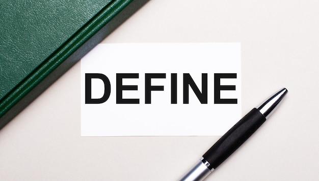 На светло-сером фоне лежит ручка, зеленый блокнот и белая карточка с текстом define. бизнес-концепция.
