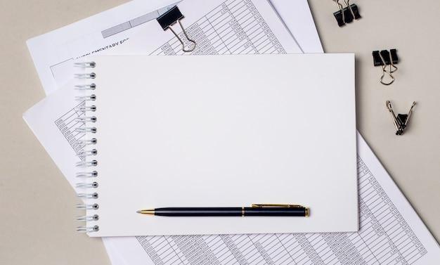 明るい灰色の背景には、レポート、黒いペーパークリップ、ペン、テキストを挿入する場所のある空白のノートブックがあります。テンプレート