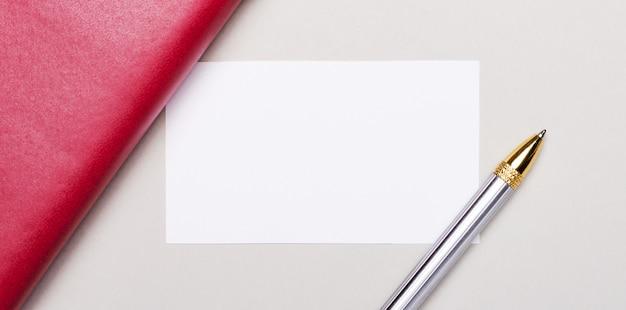 明るい灰色の背景には、金色のペン、バーガンディのノートブック、テキストを挿入する場所のある白い空白のカードがあります。ビジネスコンセプト。レンプレート