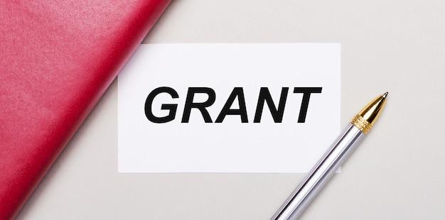 На светло-сером фоне золотая ручка, бордовый блокнот и белая пустая карточка с местом для вставки текста grant. бизнес-концепция. шаблон