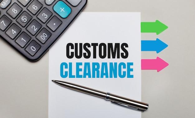 На светло-серой поверхности калькулятор, белый лист с текстом таможенный доступ, ручка и яркие разноцветные наклейки.
