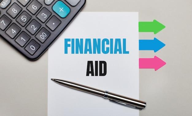 На светло-серой поверхности калькулятор, белый лист с текстом финансовая помощь, ручка и яркие разноцветные наклейки.