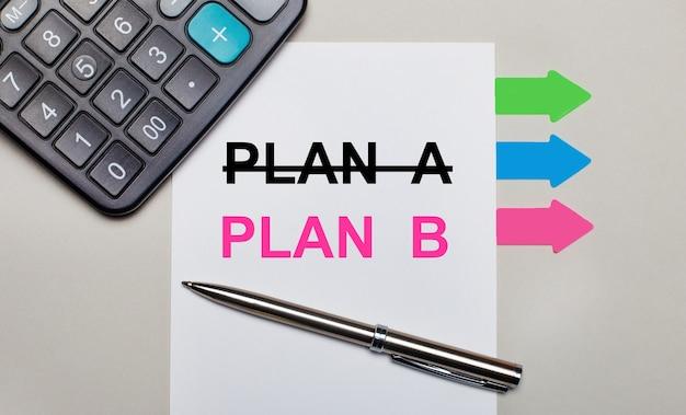 На светло-серой поверхности калькулятор, белый лист с текстом план б, ручка и яркие разноцветные наклейки.