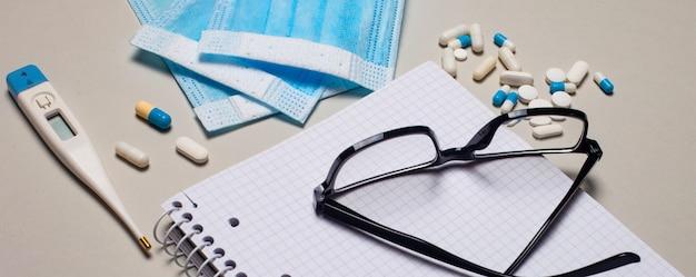 薄い灰色の表面に、使い捨てのフェイスマスク、電子体温計、丸薬、ノートブック、黒いフレームのメガネ