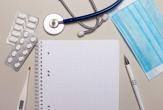 薄い灰色の表面に、水色の使い捨てフェイスマスク、聴診器、電子体温計、丸薬、ペン、テキストを挿入する場所のある空白のノートブック