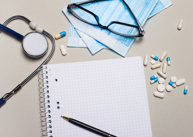薄い灰色の表面に、聴診器、丸薬、フェイスマスク、眼鏡