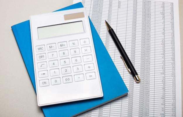 薄い灰色のテーブルには、レポート、青いノート、ペン、白い電卓があります。ビジネスコンセプト