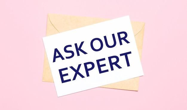 淡いピンクの背景に-クラフト封筒。それは私たちの専門家に尋ねるという白い紙を持っています。