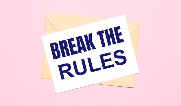 淡いピンクの背景に-クラフト封筒。 break therulesと書かれた白い紙があります