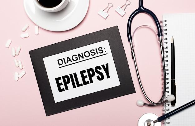 На светло-розовом фоне блокнот с ручкой, стетоскопом, белыми таблетками, скрепками и листом бумаги с текстом эпилепсия. медицинская концепция