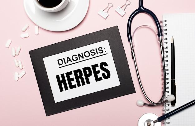 明るいピンク色の背景に、ペン、聴診器、白い錠剤、ペーパークリップ、およびテキストherpesが付いた1枚の紙が付いたノートブック。医療の概念