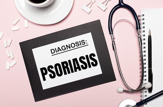 На светло-розовом фоне блокнот с ручкой, стетоскопом, белыми таблетками, скрепками и листом бумаги с текстом псориаз. медицинская концепция