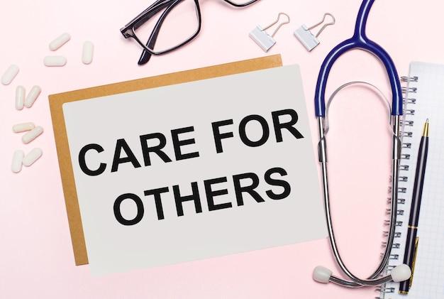 На светло-розовом фоне стетоскоп, белые таблетки и зажимы для бумаги, очки в черной оправе и лист бумаги с надписью «забота о других». вид сверху. медицинская концепция