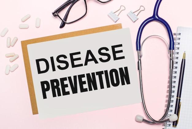 На светло-розовом фоне стетоскоп, белые таблетки и зажимы для бумаги, очки в черной оправе и лист бумаги с надписью профилактика заболеваний. вид сверху. медицинская концепция