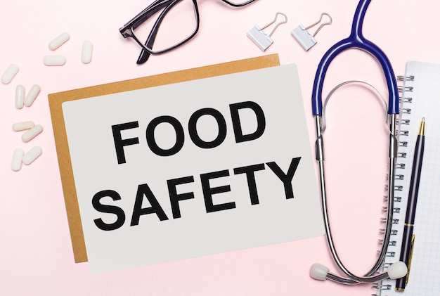 연한 분홍색 배경에 청진기, 흰색 알약, 종이용 클립, 검은색 프레임의 안경, food safety라는 텍스트가 있는 종이 한 장. 위에서 볼 수 있습니다. 의료 개념