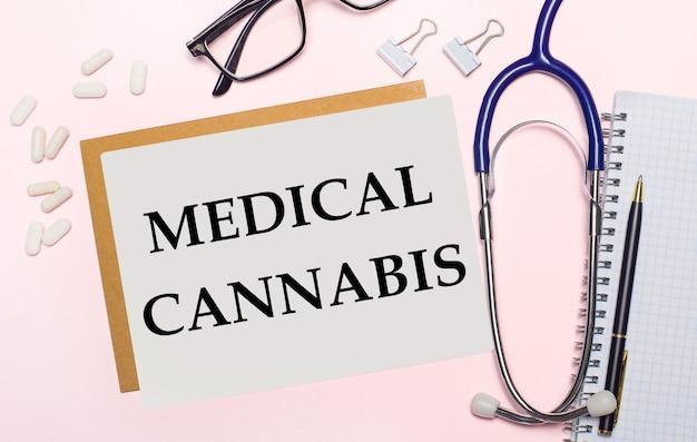 淡いピンクの背景に、聴診器、紙用の白い丸薬とクリップ、黒いフレームの眼鏡、医療大麻のテキストが書かれた一枚の紙。