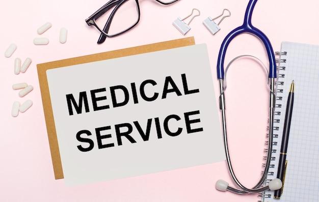 明るいピンク色の背景に、聴診器、紙用の白い錠剤とクリップ、黒いフレームの眼鏡、および「医療サービス」というテキストが書かれた一枚の紙。上からの眺め。医療の概念